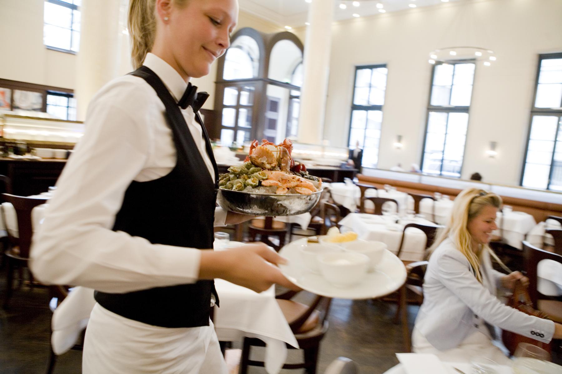 Kellnerin serviert die Meeresfruechteplatte