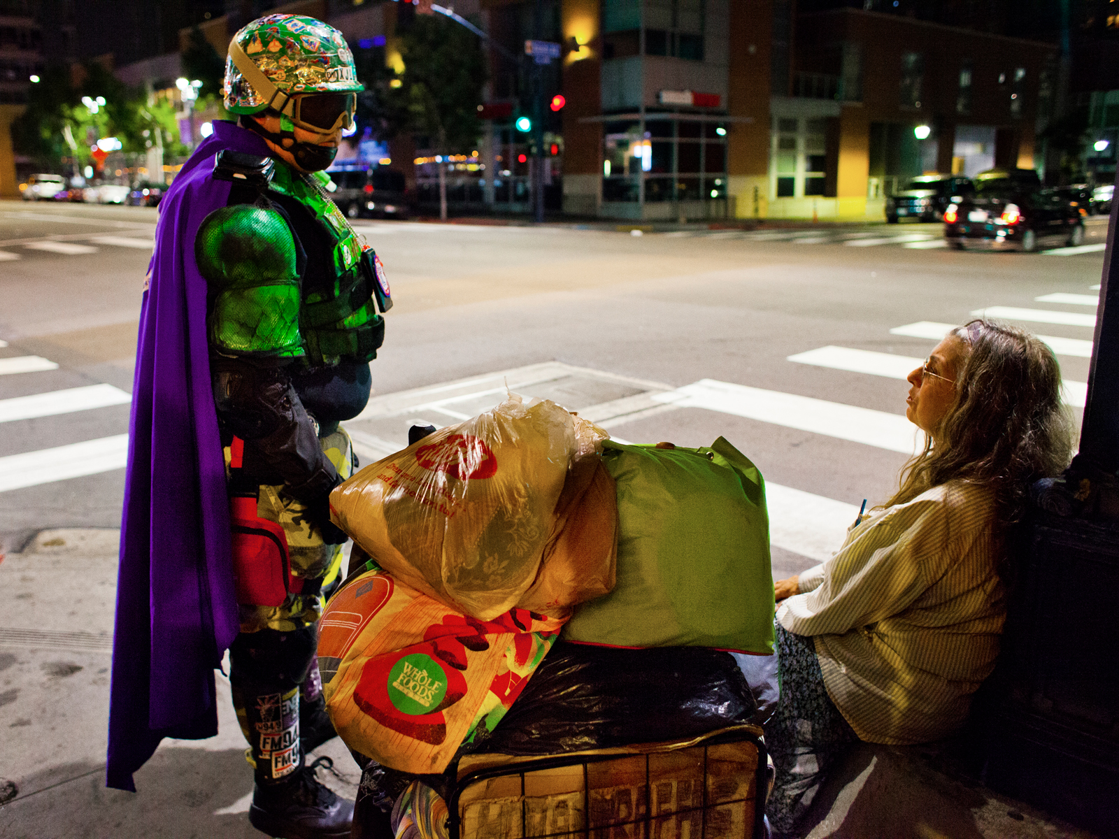Mr. Xtreme is talking to a homeless women. Everytime she meets the superheroes, she claims to have been robbed seconds ago. A lot of the homeless people are mentally ill.
